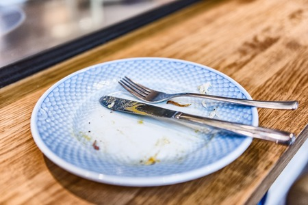 Empty plate after finished meal at restaurant - fork and knife resting on done dinner with crumbs at bistro counter.