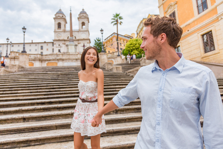 Happy romantic couple holding hands on Spanish Steps in Rome, Italy. Joyful young interracial couple walking on the travel landmark tourist attraction on romance Europe holiday vacation. Stock Photo