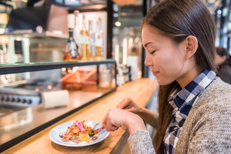 Woman eating at danish restaurant the traditional smorrebrod open sandwich at market stall counter. Happy Asian tourist trying typical meal from Denmark. Copenhagen city travel lifestyle.