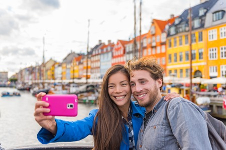 Copenhagen travel couple tourists taking selfie photo with phone camera. Smiling young people students at old port Nyhavn, tourism danish landmark in Denmark, northern Europe.