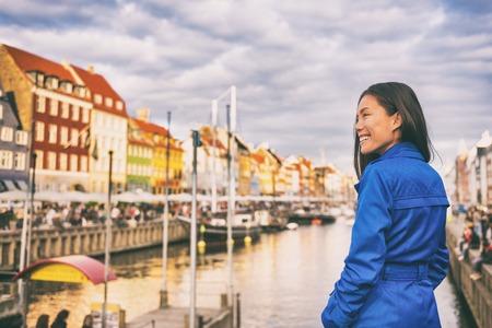Tourist in Copenhagen. Chinese Asian woman traveler walking in Nyhavn visiting Denmark. City travel, tourism in Scandinavia.