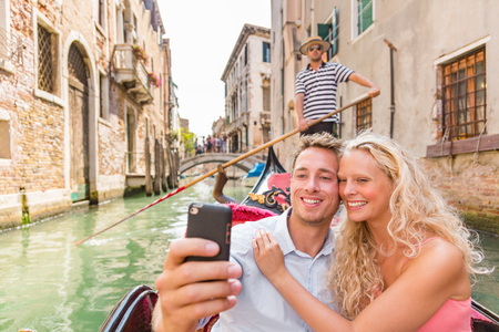 Couple taking selfie in Venice Gondola romantic boat ride happy tourists on honeymoon travel vacation holidays. Young people sailing in Venetian canal in gondola. Italy. Europe holiday.