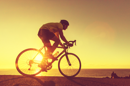 Road bike cyclist man biking on professional racing bike. Sports fitness triathlon athlete riding bike on road sunset with sun flare. Active healthy sports lifestyle athlete cycling.