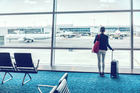 Traveler businesswoman waiting for delayed flight at airport lounge standing with luggage watching tarmac at airport window. Woman from behind at boarding gate in the morning. Travel lifestyle. Stock Photo