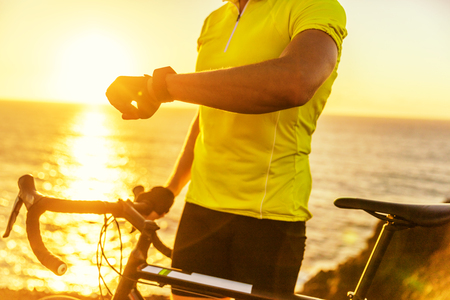 Athlete cyclist using an activity tracker gps smartwatch during biking workout in sunset nature. Road bike sports man using his watch app for fitness tracking. Healthy lifestyle.