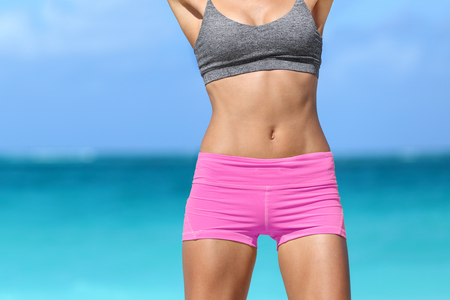 Fitness woman showing off beach body abs, weight loss diet care concept. Happy girl with slim waistline muscular body on ocean background. Stockfoto