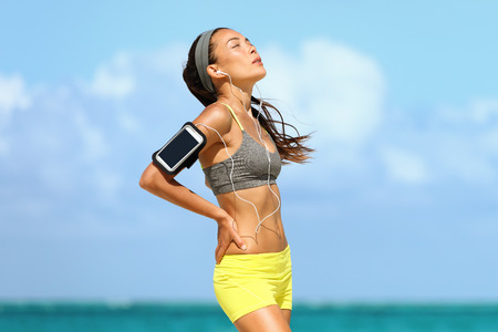 Tired woman runner on morning training at beach exhausted breathing listening to music with headphones and armband for smartphone. Heat exhaustion  dehydration concept. Stock Photo
