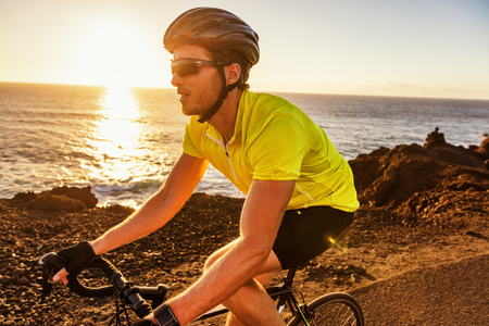Cyclist biking riding road bike in sunset training for triathlon. Athlete biker on cardio workout in outdoor nature near ocean. Sports man living an active and healthy lifestyle. Stock Photo