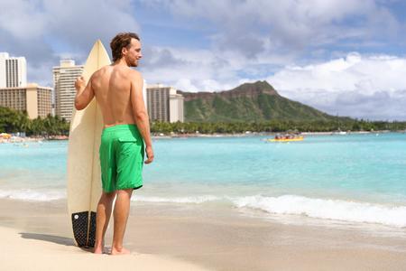 Hawaii surf man surfer surfing on Waikiki beach. Athlete standing with surfboard looking at ocean water, diamond head mountain in the landscape background, hawaiian tourist landmark. Honolulu, Oahu. 스톡 콘텐츠 - 98008676