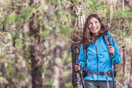 Happy hiker girl hiking in forest nature on hike trail in autumn outdoors travel vacations. Healthy lifestyle young Asian woman smiling portrait with poles, jacket, backpack. Stock fotó