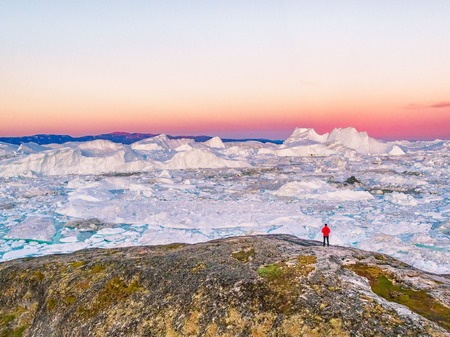 Greenland travel man tourist looking at ice landscape in sunset. Arctic destination with ice floating in ocean, aerial view.