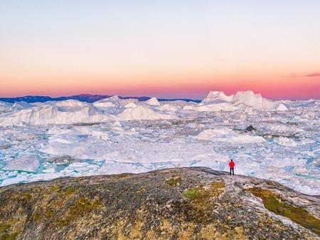 Turista dell'uomo di viaggio della Groenlandia che esamina il paesaggio del ghiaccio nel tramonto. Destinazione artica con ghiaccio che galleggia nell'oceano, vista aerea. Archivio Fotografico - 98008717