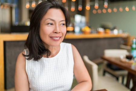 Happy healthy Asian middle-aged business woman relaxing inside restaurant. Beautiful mature Chinese business woman portrait in fancy restaurant in Shanghai, China. Beauty aging skin care.