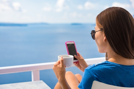 Phone morning breakfast woman drinking coffee cup on Europe summer vacation relaxing girl at cafe reading cellphone at outdoor terrace view of Ocean in Santorini, Greece. European destination holiday.