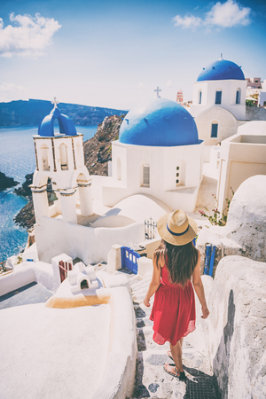 Travel destination europe tourist girl walking in Santorini at the three blue domes, famous Greek landmark. Oia village, Santorini island, luxury vacation. 写真素材