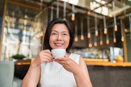 Asian middle aged woman drinking cappuccino coffee at high end fancy cafe. Chinese businesswoman enjoying cup of tea during afternoon at restaurant.