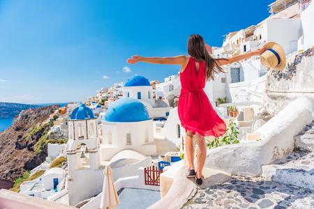 Europa-Reiseferienspaß-Sommerfrauentanzen in der Freiheit mit den Armen oben glücklich in Oia, Insel Santorini, Griechenland. Sorgloser Mädchentourist im europäischen Bestimmungsort, der rotes Modekleid trägt. Standard-Bild