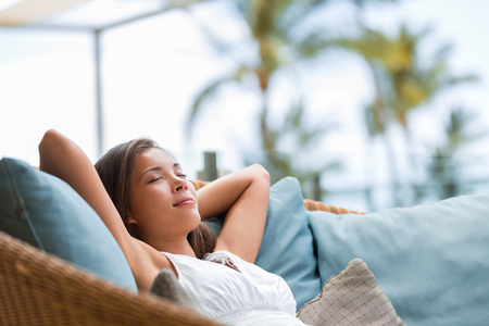 Home lifestyle woman relaxing sleeping on sofa on outdoor patio living room. Happy lady lying down on comfortable pillows taking a nap for wellness and health. Tropical vacation.