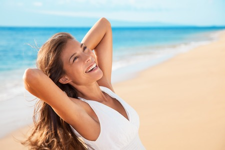 Smiling happy mixed race woman enjoying serene sunset. Carefree Asian woman relaxing on beach travel holidays vacation. Freedom and wellness concept. Banque d'images