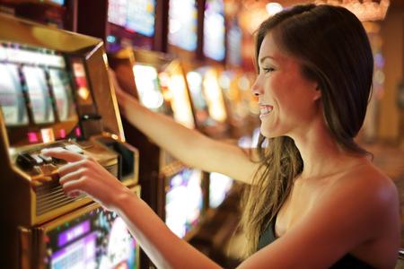 Asiatische Frau, die im Kasino spielt, das auf Spielautomaten spielt, die Geld ausgeben. Spieler süchtig nach Spinnmaschine. Asiatische Spielerin, Nachtleben Lebensstil. Las Vegas, USA.