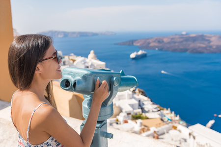 Travel tourist on Europe holiday walking in Santorini city street looking through tower viewers coin machine, binoculars to watch cruise ships in Mediterranean sea.