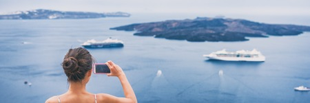 Travel tourist taking holiday picture with phone of cruise ships in Mediterranean sea in Santorini, Greece. Europe vacation destination banner panorama. Stock Photo