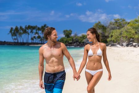Playa vacaciones de verano traje de baño traje de baño pareja caminando juntos divirtiéndose en viajes de vacaciones tropicales. Gente multirracial sexy disfrutando del bronceado.