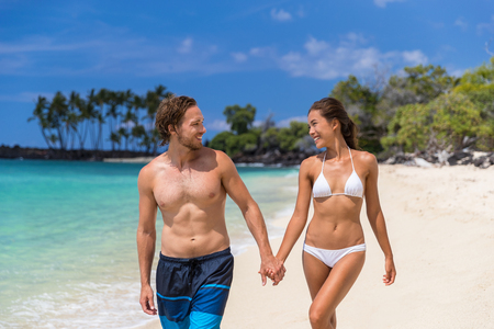 Beach summer vacation swimwear swimming suit couple walking together having fun on tropical holiday travel. Sexy multiracial people enjoying suntan.
