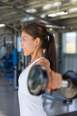 Gym woman fitness training arms lifting free weights. Dumbbell lateral raise shoulder workout. Stock Photo