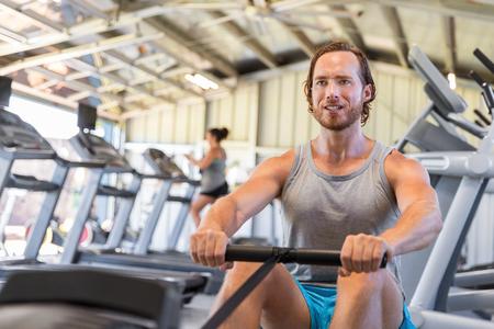 Man athlete training cardio on rowing machine in fitness gym.