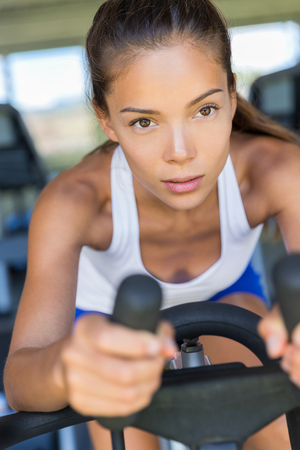 Asian woman training cardio workout at home on indoor bike. Working out to get in shape. Concept for weight loss. Motivated and focused young girl.