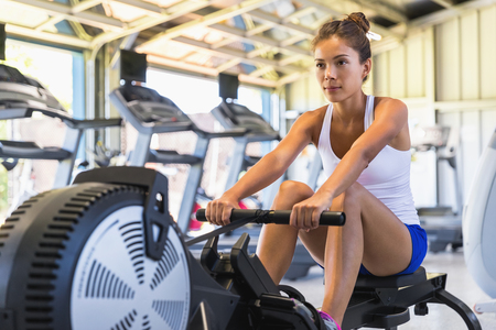 Workout woman cross training exercising cardio using rowing machine in fitness gym. Asian girl working out.