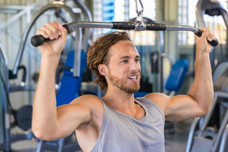 Shoulder pull down machine. Fitness man working out lat pulldown training at gym. Upper body strength exercise for the upper back. Stock Photo