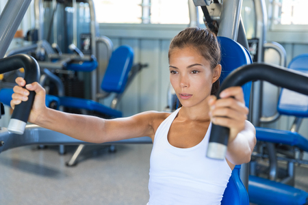 Gym workout Asian woman focused and motivated training on pec deck fly machine. Fitness workout.