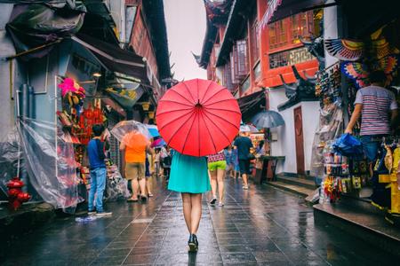 차이나 타운 쇼핑 거리에서 걷는 사람들 여자. 중국에 좁은 골목에 빨간 동양 우산 아래 비오는 날 여자 관광 상하이 여행.