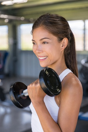 Asian woman strength training biceps with free weights at gym, lifting dumbbells for arm workout. Stock fotó