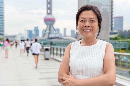 Retrato sonriente feliz empresaria asiática de mediana edad. Hermosa mujer de negocios chinos maduros en Shanghai, China.