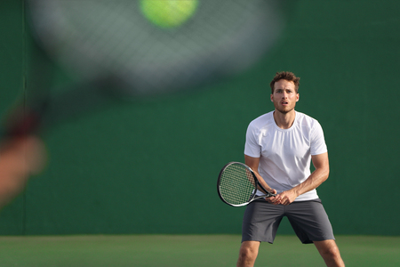 Tennis player focused on other player hitting ball with racket on court.