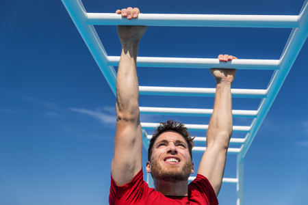 Athlete working out gripping climbing on ladder equipment at sport athletics centre. Stock Photo