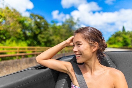 happy smiling Asian woman sitting in passenger seat of convertible cabriolet with safety belt. Stock Photo