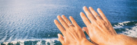 Cruise honeymoon travel vacation for newlyweds couple showing wedding rings on hand selife at ocean view resort background.