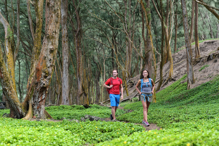 Hiking couple tourists walking together in forest trail path in summer travel vacation destination in Hawaii. Stock Photo