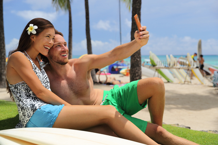 Selfie couple taking phone picture on Hawaii Waikiki beach travel vacation. Stock Photo