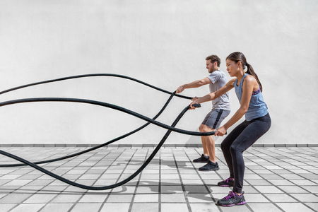 Woman and man couple training together doing battling rope workout Foto de archivo