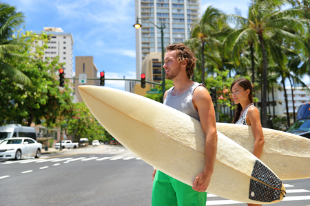 Honolulu Hawaii lifestyle surfers people walking in city with surfboards going to the beach surfing.