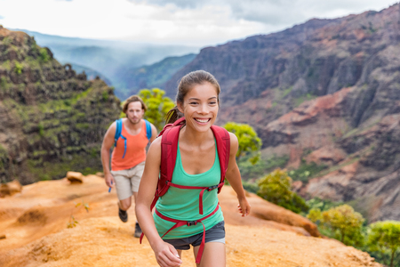 Young woman and man hikers walking in mountain nature landscape in mountains.