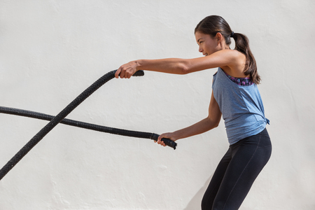 Fitness woman training battle ropes workout at gym.