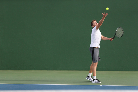 Tennis serve player man serving ball during match point on outdoor green court. 免版税图像
