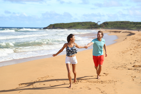 Hawaii beach couple on summer travel vacation running having fun laughing carefree in tropical destination, Kauai, Hawaii, USA.