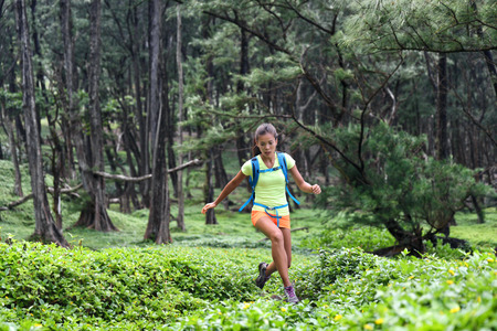 Trail runner woman athlete running jumping in forest nature mountains background.